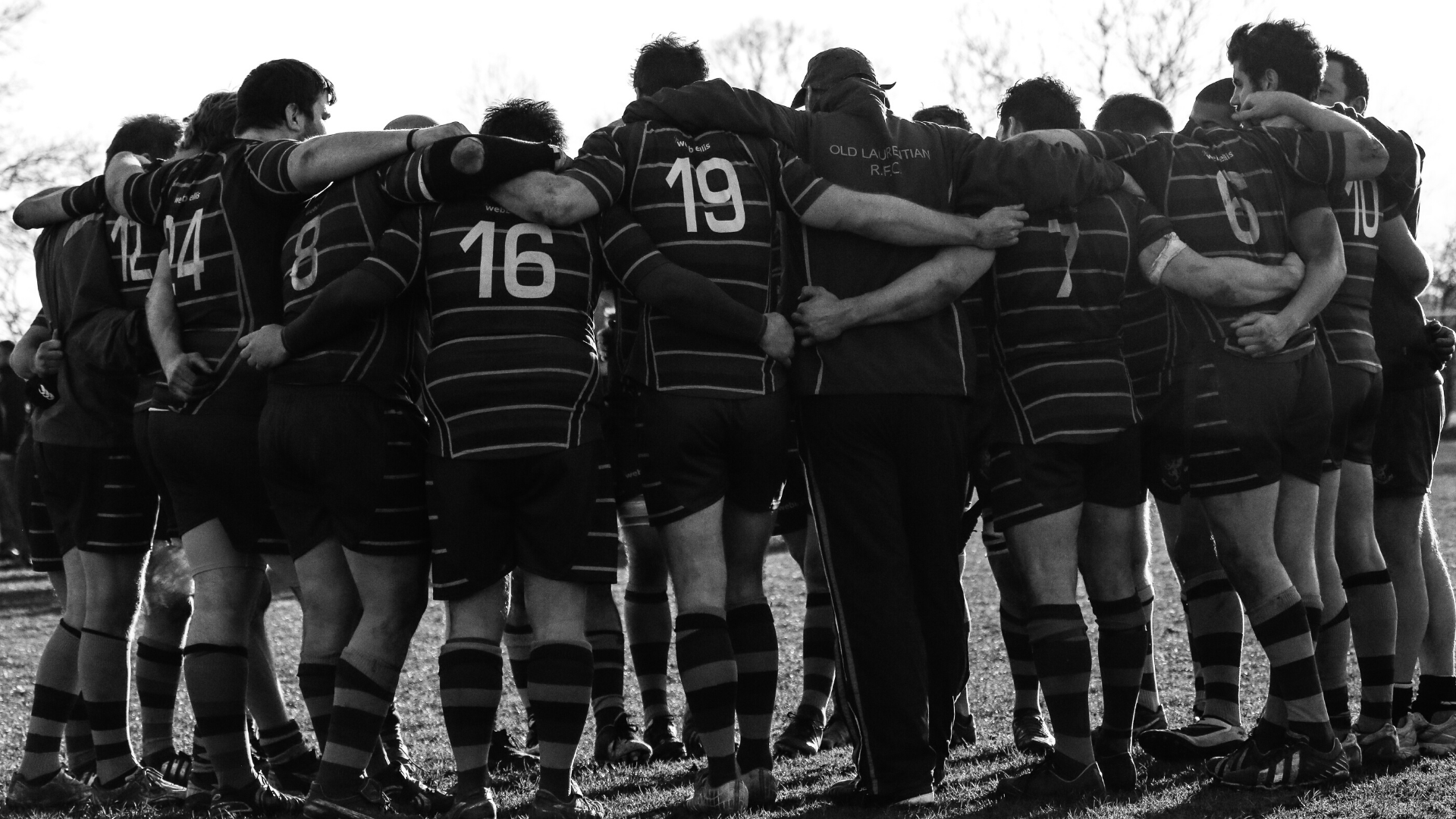 Show a rugby team in a huddle